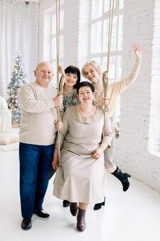Mãe de meia-idade sorridente sentada no balanço, pai e duas jovens lindas irmãs se divertindo