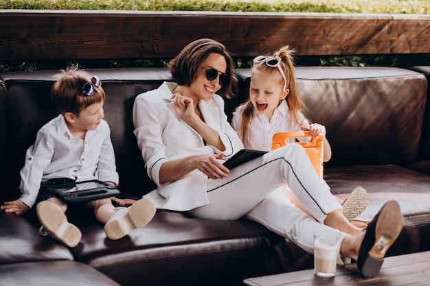 Mãe de mulher de negócios trabalhando em casa com filhos