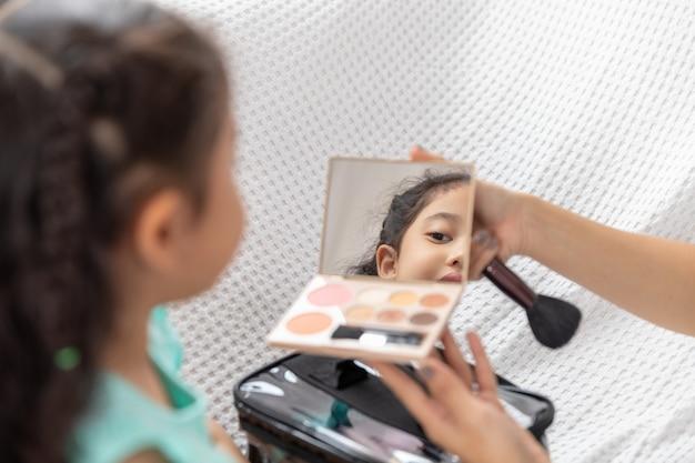 Mãe de mulheres de ásia e filha jogando maquiagem no sofá da casa