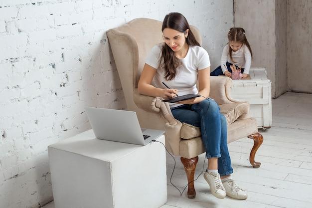 Mãe de negócios trabalhando com laptop em casa enquanto a filha de desenho. negócios, maternidade, multitarefa e conceito de família.