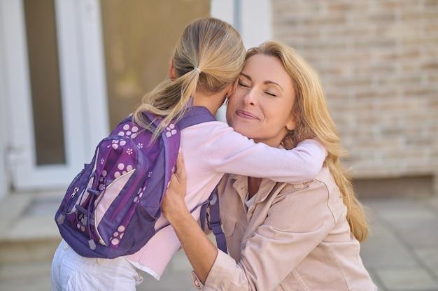 Mãe de olhos fechados abraçando a filha