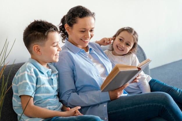 Mãe de plano médio lendo para crianças