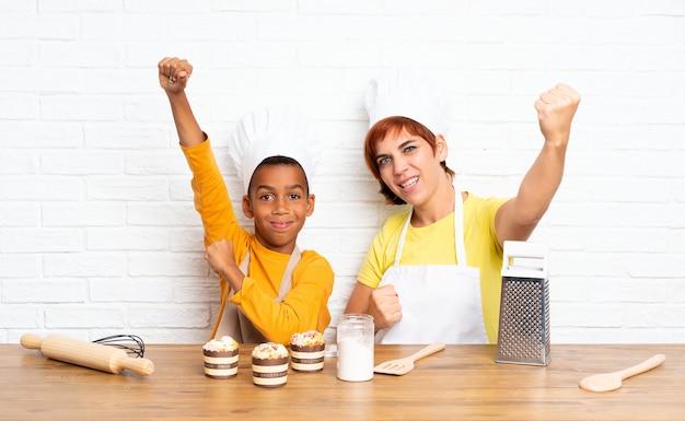 Mãe de sorte e seu filho vestido como chef em uma cozinha