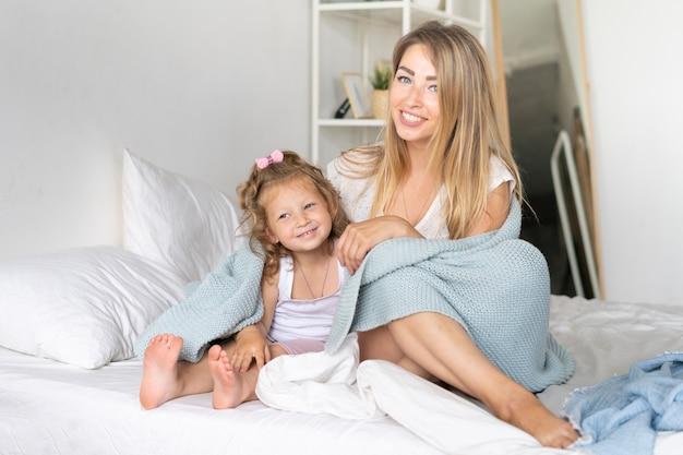 Mãe de tiro completo sentado na cama com a filha