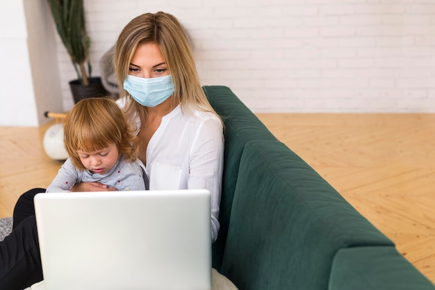 Mãe de tiro médio com máscara segurando criança
