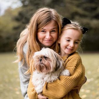 Mãe de tiro médio e filha abraçando um cachorro