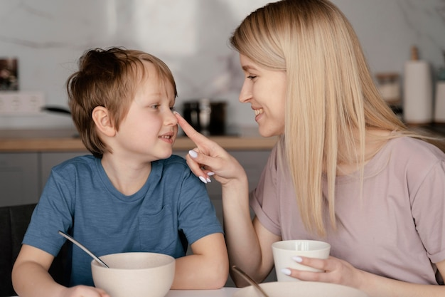Mãe de tiro médio e filho na mesa