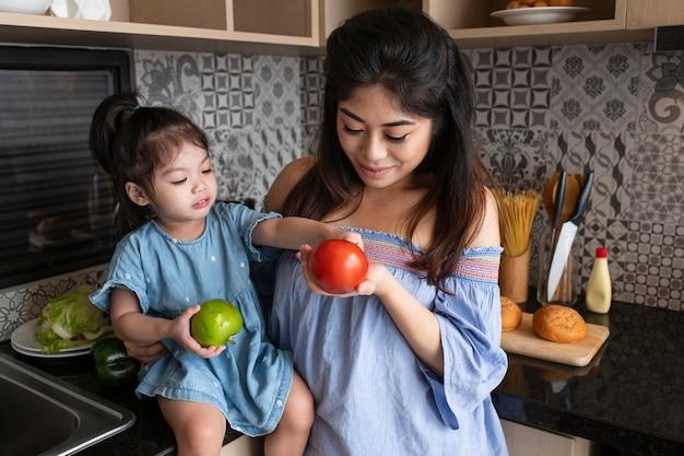 Mãe de tiro médio e menina na cozinha