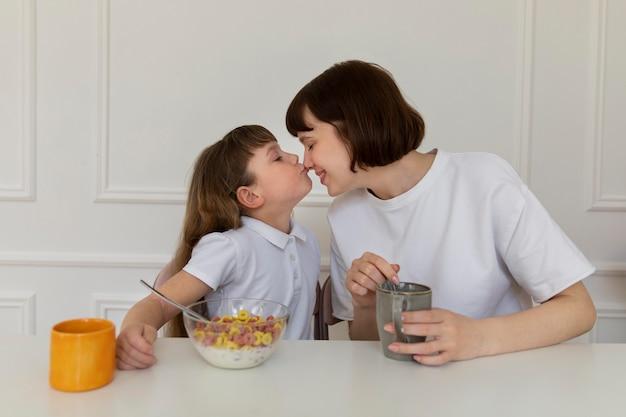 Mãe de tiro médio e menina sentadas à mesa