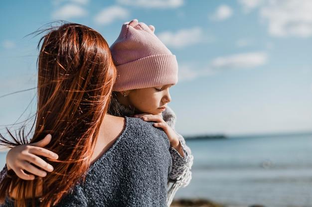 Mãe de tiro médio segurando a filha