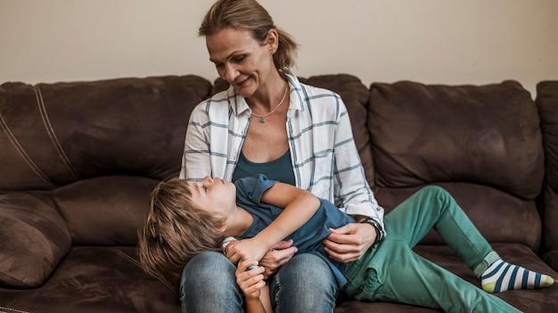 Mãe de tiro médio segurando criança dentro de casa