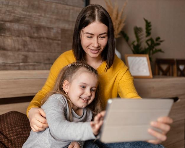 Mãe de tiro médio segurando criança e laptop