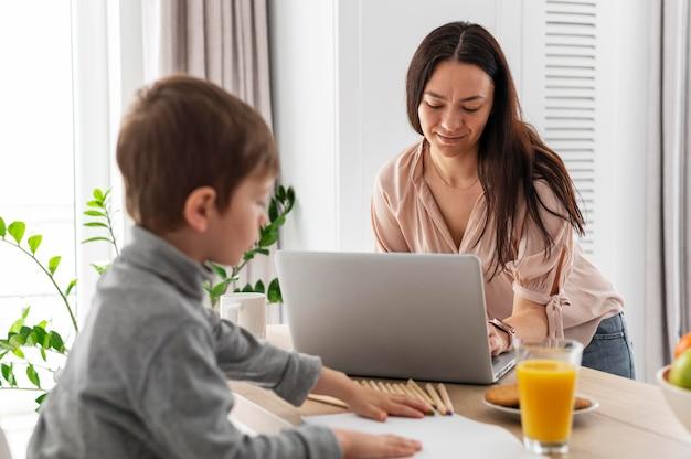 Mãe de tiro médio trabalhando com laptop