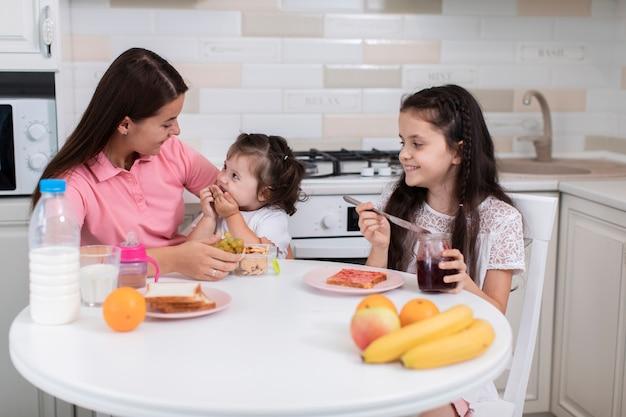 Mãe de vista frontal com filhas na cozinha