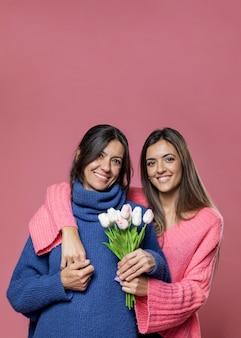 Mãe de vista frontal com flores da filha