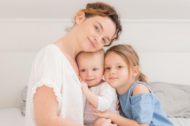 Mãe de vista frontal posando com crianças