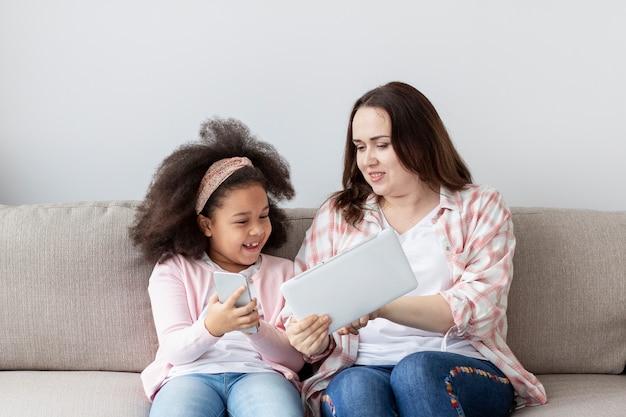 Mãe de vista frontal relaxante com a filha em casa