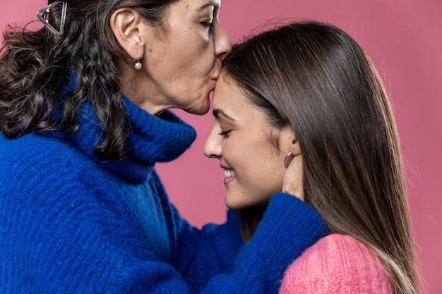 Mãe de vista lateral beijando filha
