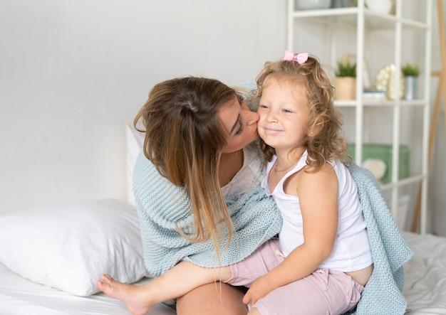 Mãe de vista lateral beijando sua filha