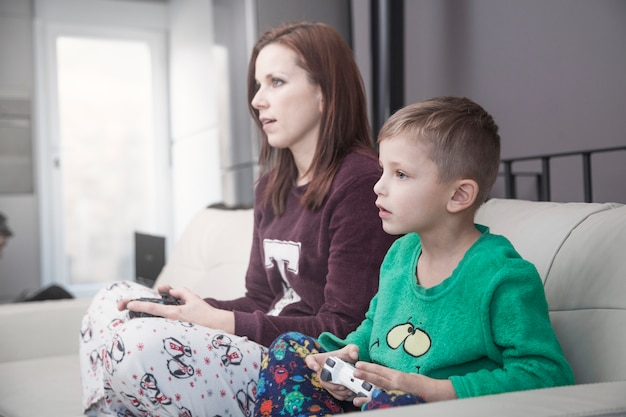 Mãe de vista lateral e filho jogando videogame
