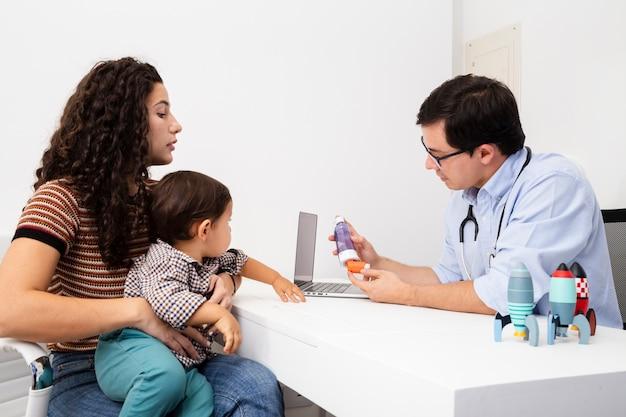 Mãe de vista lateral prestando atenção na visita de um médico