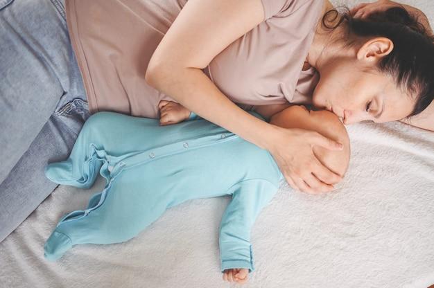 Mãe deita-se com bebê recém-nascido em macacão azul abraçando e amamentando com leite materno