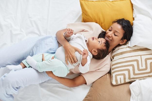 Mãe deitada com a criança na cama
