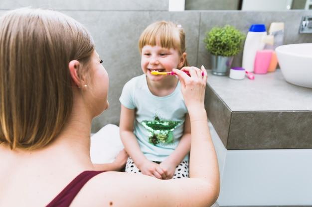 Mãe, dentes escovando, de, menina