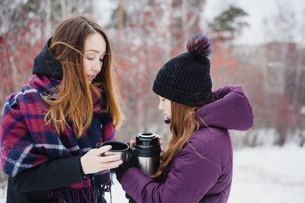 Mãe derrama chá quente ou bebe uma garrafa térmica para a filha, caminhada de inverno, inverno