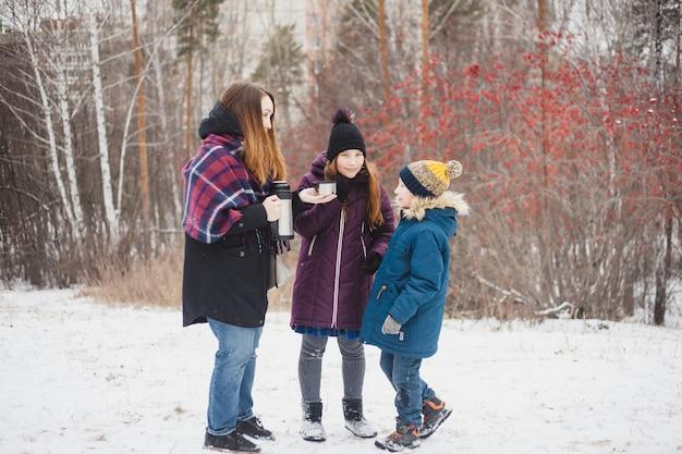 Mãe derrama chá quente ou bebe uma garrafa térmica para a filha e o filho, caminhada no inverno, inverno