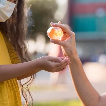 Mãe derramando desinfetante para a filha