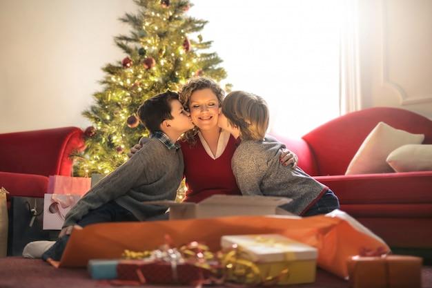 Mãe desembrulhando presentes com seus filhos