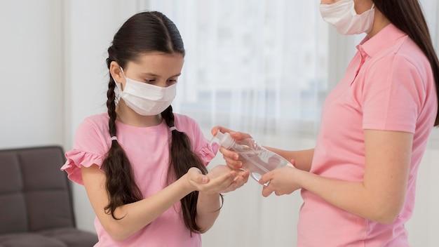 Mãe despejando desinfetante nas palmas das mãos