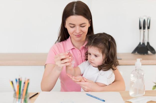 Mãe despejando desinfetante para menina