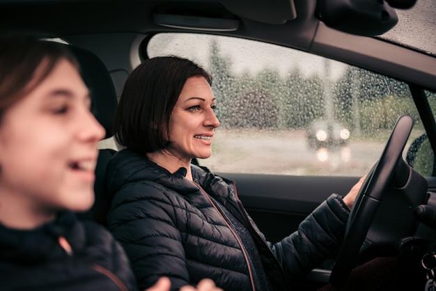 Mãe dirigindo filha no banco do passageiro em um dia chuvoso