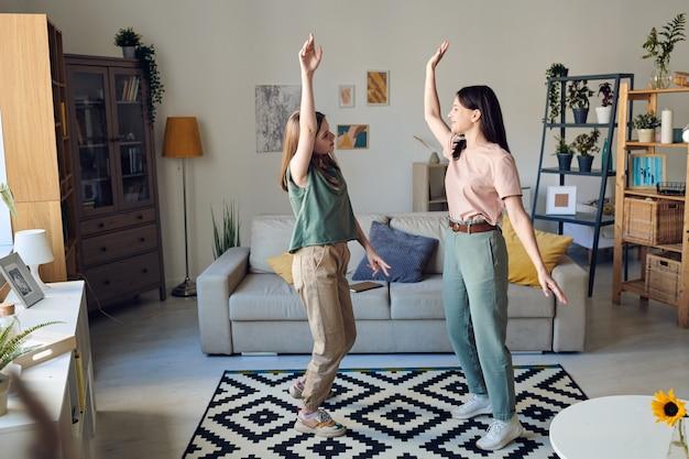 Mãe divertida e filha adolescente dançando na sala de estar enquanto aproveitam o lazer juntas