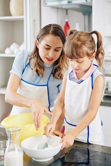Mãe dizendo à filha quanto açúcar adicionar na tigela quando ela estiver fazendo massa de bolo