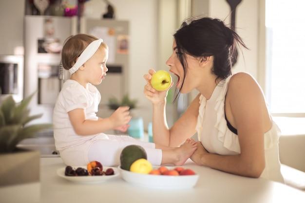 Mãe doce, alimentando seu bebê na cozinha