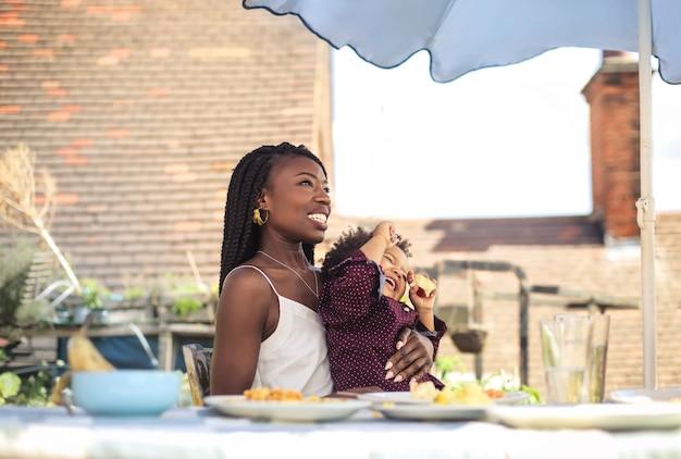 Mãe doce almoçando no terraço com seu filho