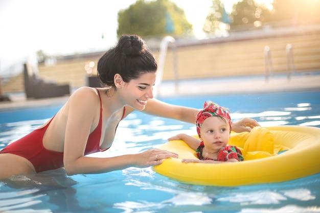 Mãe doce, aproveitando o tempo com seu bebê na piscina