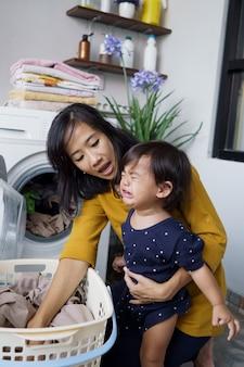Mãe dona de casa com um bebê chorando na lavanderia de casa