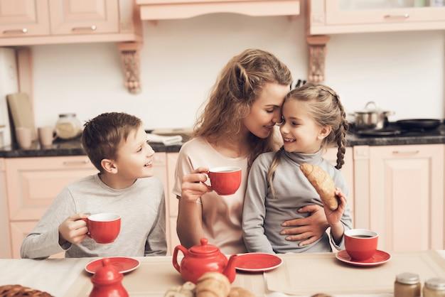 Mãe dos pais solteiros kids have tea with croissants.