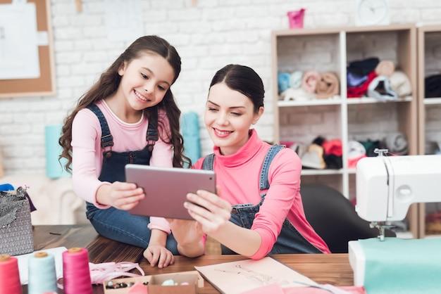 Mãe e a menina olham tablet juntos.