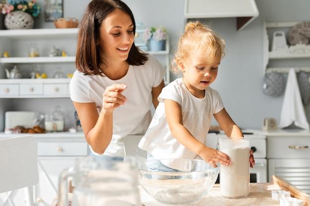 Mãe e adorável menina cozinhando juntos