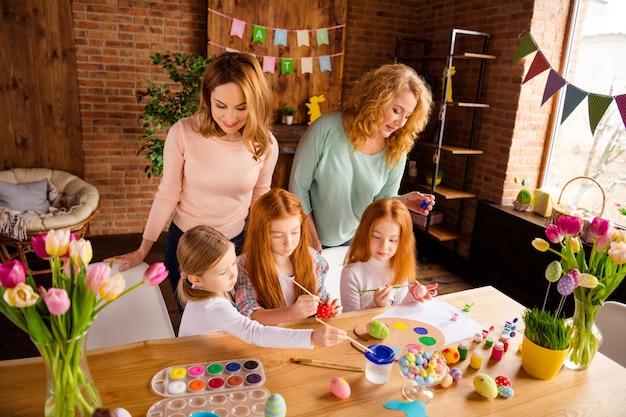 Mãe e avó com crianças pintando