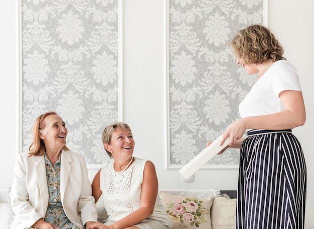Mãe e avó olhando sua filha segurando o álbum de fotos em casa