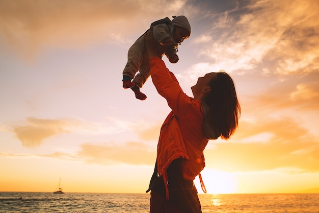 Mãe e bebê ao pôr do sol praia oceano mulher e criança juntos no mar fundo de família feliz