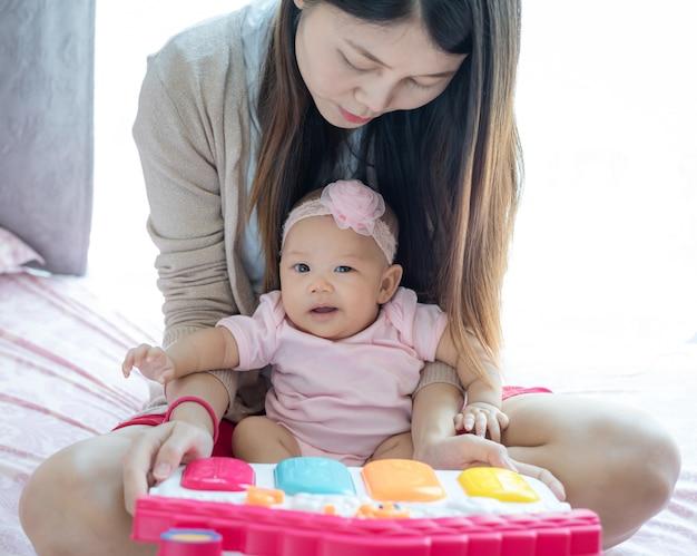Mãe e bebê brincando brinquedo na cama.