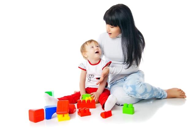 Mãe e bebê brincando com um brinquedo de blocos de construção