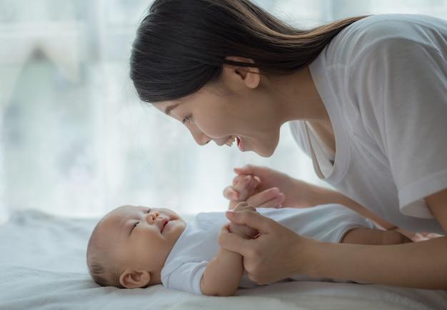 Mãe e bebê brincando no quarto. pai e filho relaxando em casa. família se divertindo juntos.